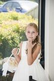 有篮子的美丽的女花童在窗口附近 图库摄影