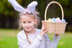 有篮子的逗人喜爱的小女孩佩带的兔宝宝耳朵有很多复活节彩蛋在春日户外 免版税库存图片