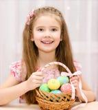有篮子的逗人喜爱的微笑的小女孩有很多复活节彩蛋 免版税库存照片