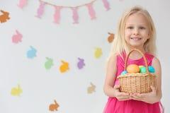 有篮子的逗人喜爱的滑稽的女孩有很多复活节彩蛋 免版税库存图片