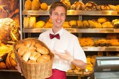 有篮子的贝克有很多面包在面包店 免版税库存照片