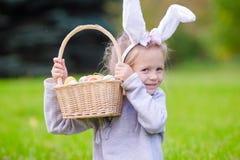 有篮子的画象小女孩有很多复活节彩蛋在户外春日 免版税库存图片