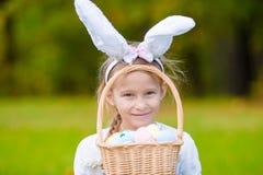 有篮子的画象小女孩有很多复活节彩蛋在户外春日 库存照片