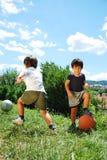 有篮球和橄榄球的二个小孩 免版税库存照片