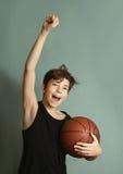有篮球球比分目标姿态的Teeb男孩 库存图片