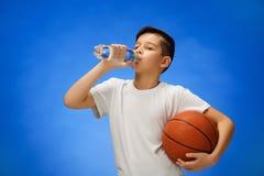 有篮球球的可爱的11岁的男孩孩子 图库摄影