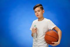 有篮球球的可爱的11岁的男孩孩子 免版税库存图片