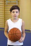 有篮球球的青少年的男孩在健身房 库存图片
