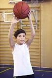 有篮球球的青少年的男孩在健身房 免版税库存照片