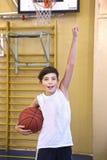 有篮球球的青少年的男孩在健身房 免版税库存图片