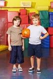 有篮球的两个男孩在学校健身房  库存图片