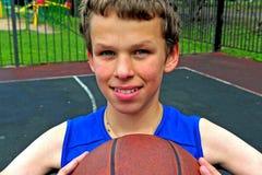 有篮球的微笑的男孩坐法院 免版税库存照片