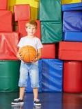 有篮球的男孩在健身房 库存图片