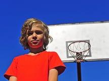 有篮球篮的愉快的微笑的男孩在背景 图库摄影