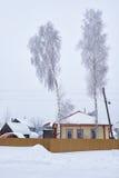 有篱芭和桦树的西伯利亚私有房子在雪下 免版税库存图片