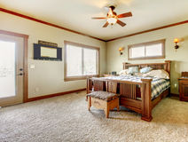 有米黄地毯和绿色墙壁的自然客舱农厂房子卧室。 库存照片