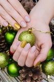 有米黄钉子设计的美好的女性手 圣诞节修指甲 图库摄影