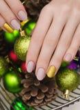 有米黄钉子设计的美好的女性手 圣诞节修指甲 免版税库存照片