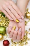 有米黄钉子设计的美好的女性手 圣诞节修指甲 库存照片