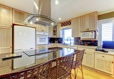 有米黄内阁和白色天花板的明亮的舒适厨房 免版税库存图片