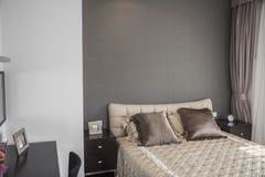 有米黄床罩的明亮,现代卧室。 免版税库存照片