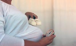 有米黄羊毛baby&的x27怀孕的腹部; 对此的s鞋子 免版税图库摄影