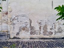有粉碎的白色膏药和大卵石的老墙壁在庭院里 库存图片