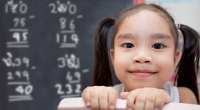 有粉笔画数学演算的女孩对黑板 库存照片