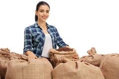 有粗麻布大袋的女性农业工作者用咖啡填装了 免版税库存图片