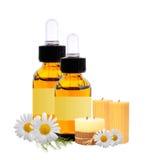 有精华的瓶上油,在whi和春黄菊隔绝的蜡烛 免版税库存图片