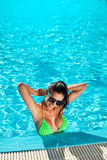 有精密乳房的逗人喜爱的愉快的比基尼泳装妇女在游泳池 库存照片