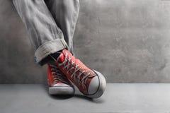 有精密运动鞋的灰色牛仔裤在具体背景 免版税库存照片