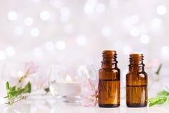 有精油、花和蜡烛的两个瓶在与bokeh作用的白色桌上 温泉,芳香疗法,健康,秀丽题材 免版税图库摄影