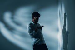 有精神分裂症的人单独站立在屋子里指向他的在墙壁,真正的照片上的阴影的 免版税库存图片