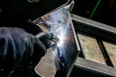 有精采明亮的白色星的人手工氩弧焊钢板破裂了绽放 库存图片