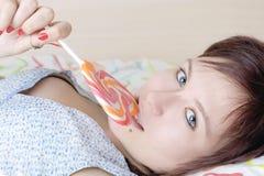 有糖果棒棒糖的女孩在她的嘴 免版税图库摄影