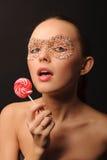 有糖果面具的性感的妇女在面孔 库存照片