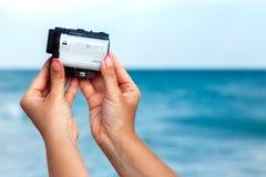 有索尼行动凸轮的X3000女性手射击录影在seasi 免版税库存图片