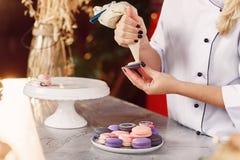 有紧压奶油的糖果店袋子的手对macarons壳 免版税图库摄影