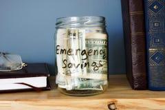 有紧急储款现金资金的瓶子在架子 免版税库存图片