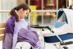 有紫罗兰色女用披肩的年轻欧洲妇女在公共场所购物的mal哺乳她的接近白色婴儿车的小孩 库存图片
