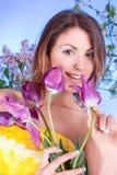 有紫罗兰色郁金香花的秀丽少妇 免版税库存图片