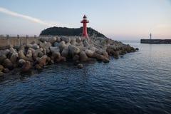 有紫色光的红色和白色灯塔在与wavebreakers的一座防波堤在日落期间在西归浦,济州海岛,韩国 库存照片