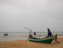 有紫色旗子的乌贼渔船在海滩在多云早晨天,有海背景 免版税库存图片