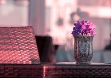 有紫色花花束的玻璃花瓶在书桌上的 免版税库存图片