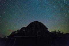 有繁星之夜天空的老谷仓与云彩和银河在su 库存图片
