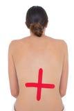 有红十字标志后面的露胸部的适合妇女 免版税库存图片