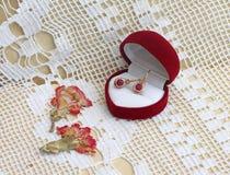 有红宝石ââin礼物盒的金耳环 免版税库存照片