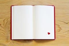 有红心的开放笔记本在木背景 免版税库存图片