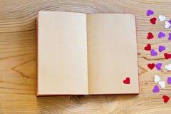 有红心的开放笔记本在木背景 免版税库存照片